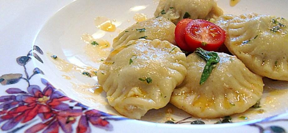 Ravioli mit Kirschtomate und Butter auf einem Blumenteller