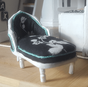 Miniature chaise relaxing outside a kitchen =D