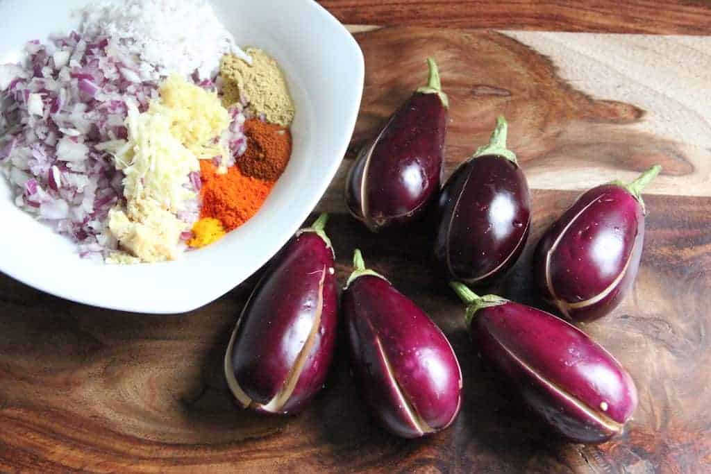 Baby eggplant with vertical slits and a white bowl with the ingredients for the stuffing.