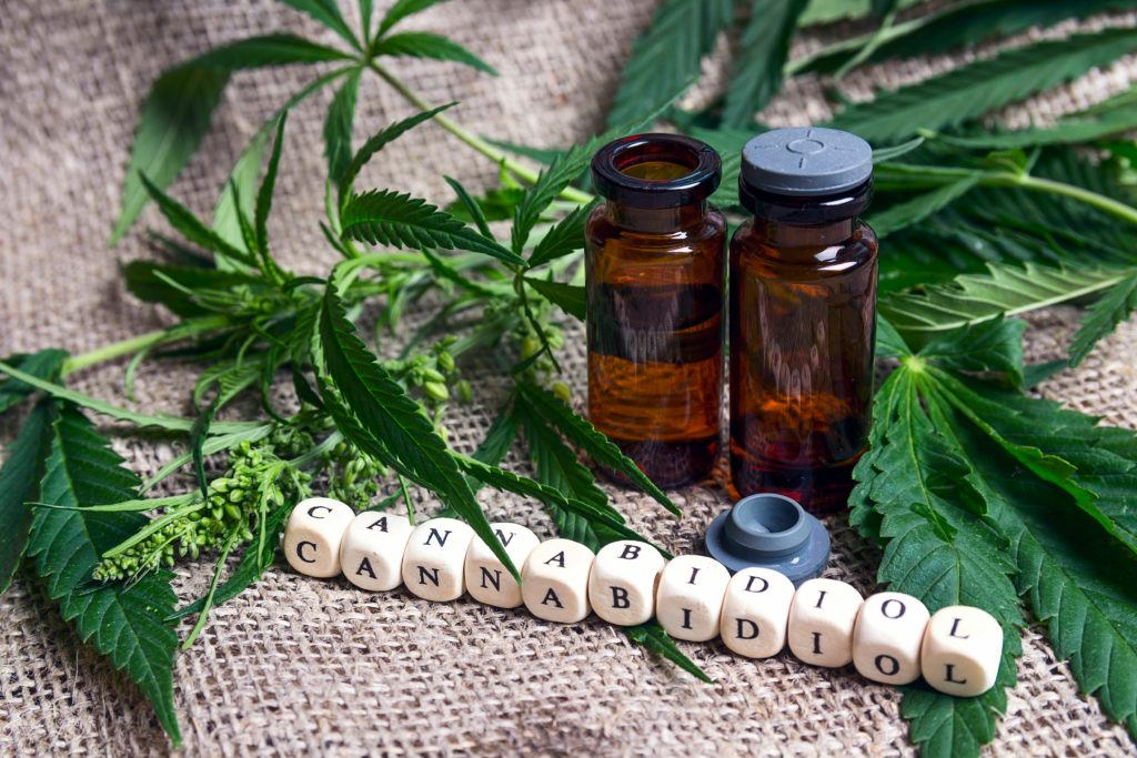 Is CBD safe and does it have side effects? Photo: Image shows two bottls of CBD, hemp leaves, and some letter blocks spelling out cannabidiol.