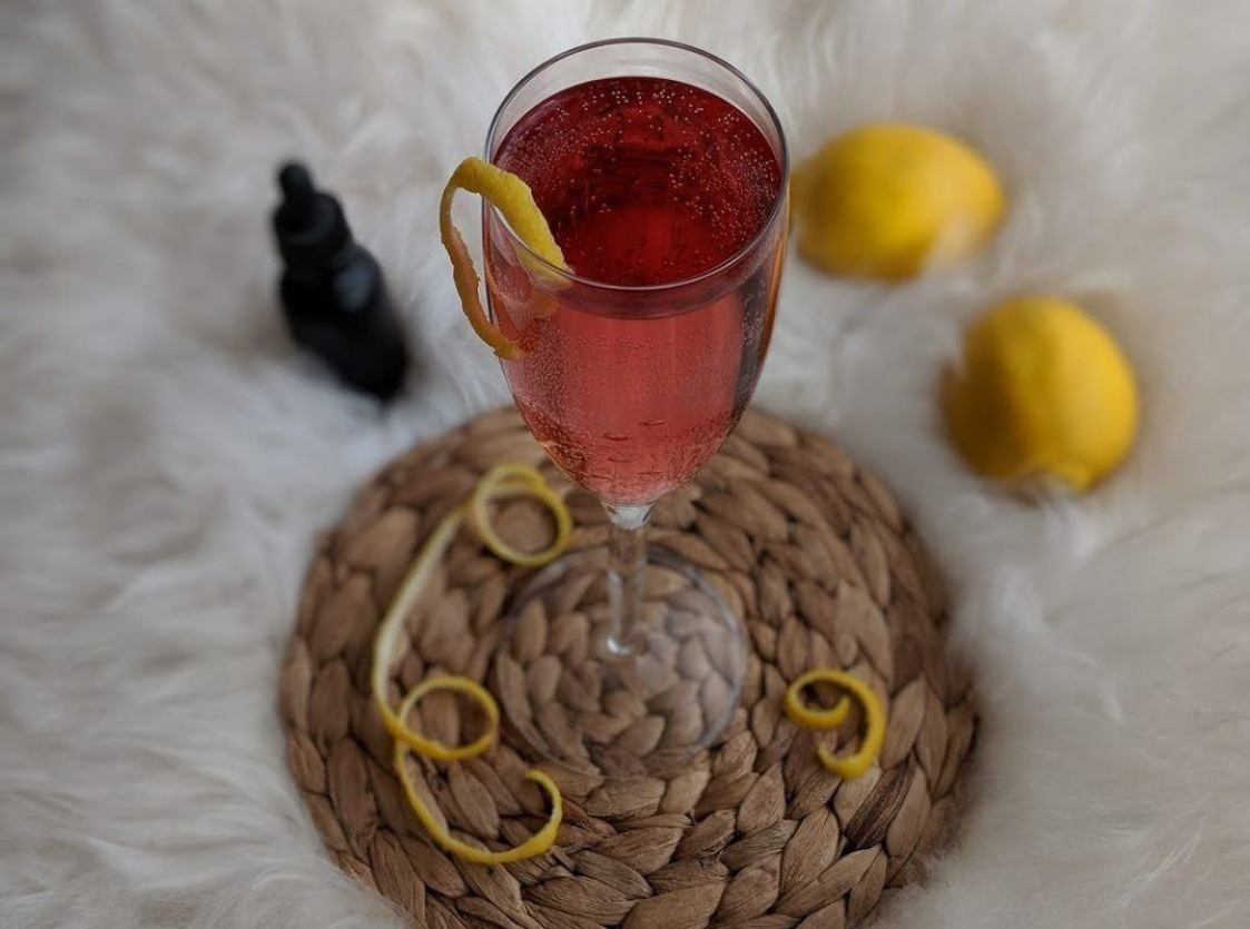 A pink cocktail in a champagne glass, garnished with a lemon twist, sits atop a woven drink coaster. Nearby are lemons and a bottle of CBD. Our sparkling CBD cocktail mixes the terpenes and flavonoids of CBD oil with sweet citrus and tart cranberry for an elevated New Years.