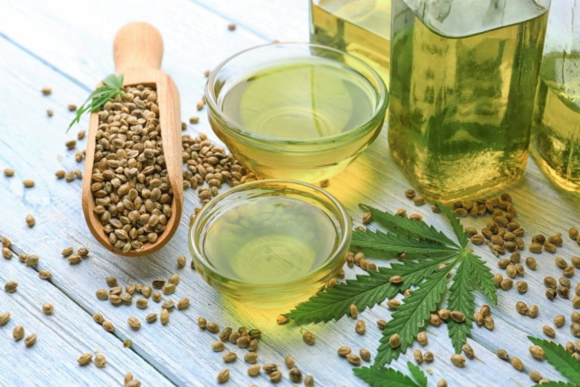 An overflowing scoop of hemp seeds sits near a bowl of hemp seed oil and two bottles of vegetable oil, along with a hemp leaf. CBD tinctures typically combine hemp extract with a carrier oil such as hemp seed oil, MCT oil, or even olive oil.