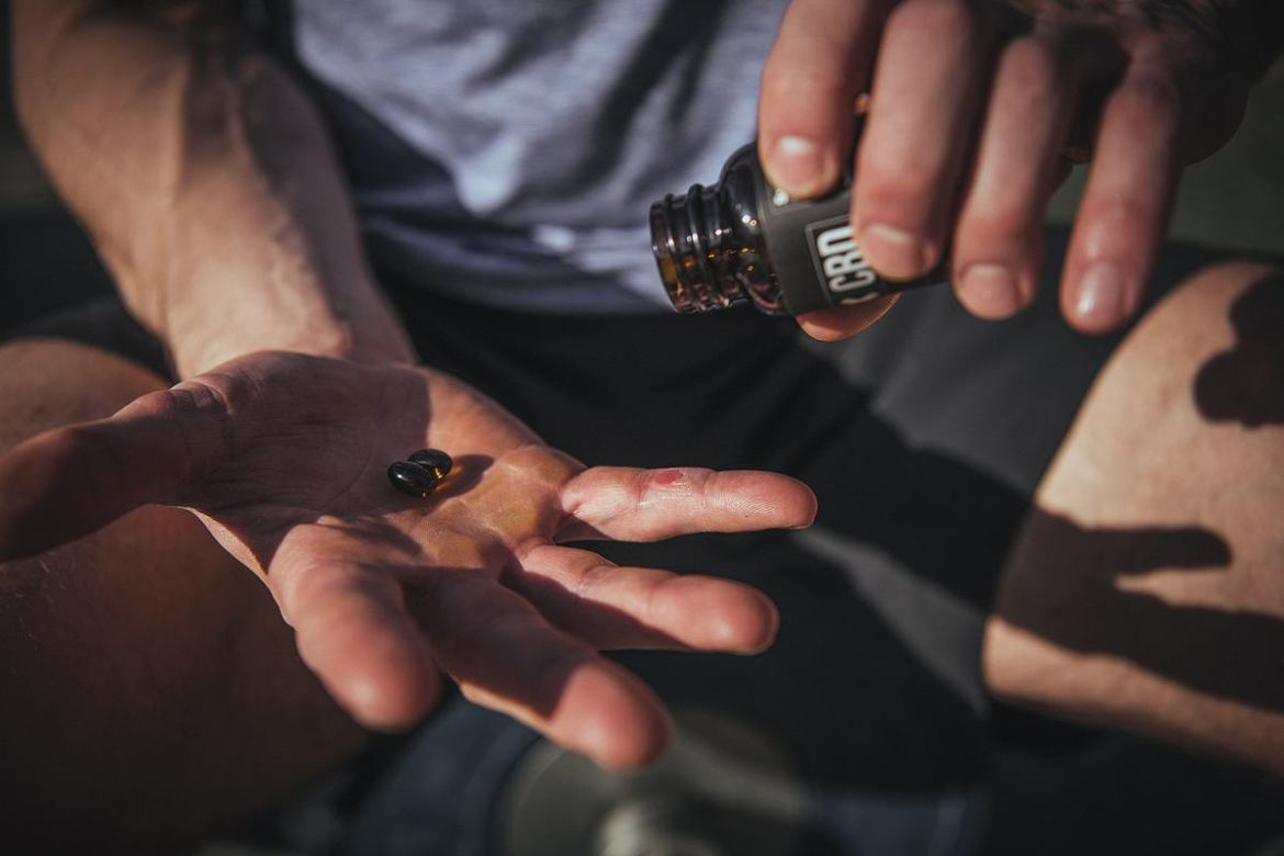 Photo: An athlete holds CBD capsules in their hand.