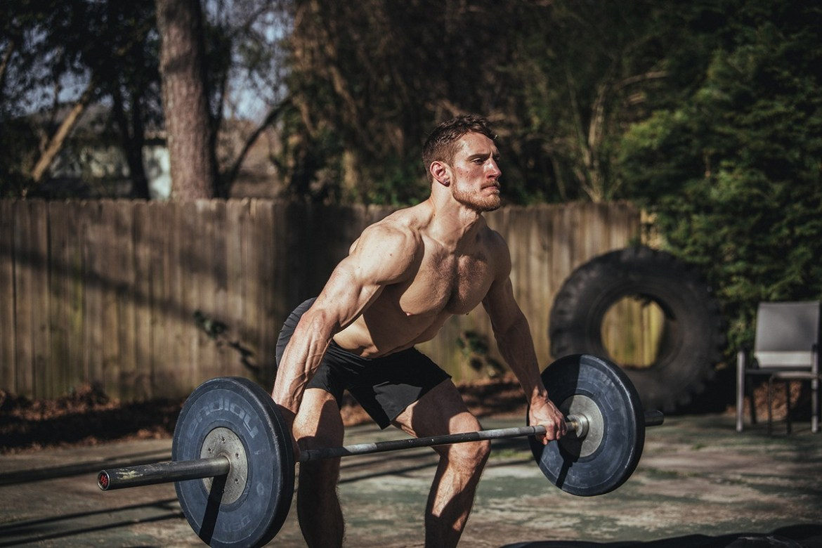 Photo: A muscular shirtless man lifts a large weight outdoors.