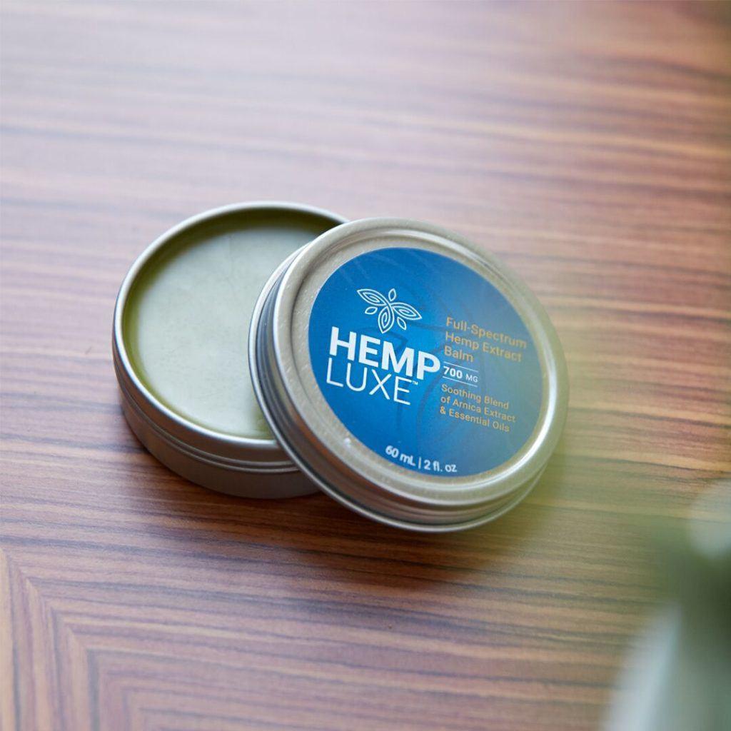 Photo: HempLuxe Hemp Extract Balm rests open on a wooden tabletop.