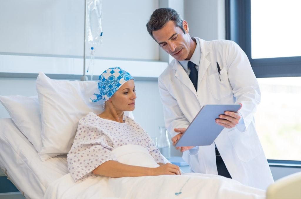 While rare, CBD can interfere with a few medications. It's always important to consult with a medical professional before adding CBD to your supplement routine. Photo: A doctor consults with a woman in a hospital bed, holding a clipboard. She has a hair wrap on due to cancer treatment hair loss.