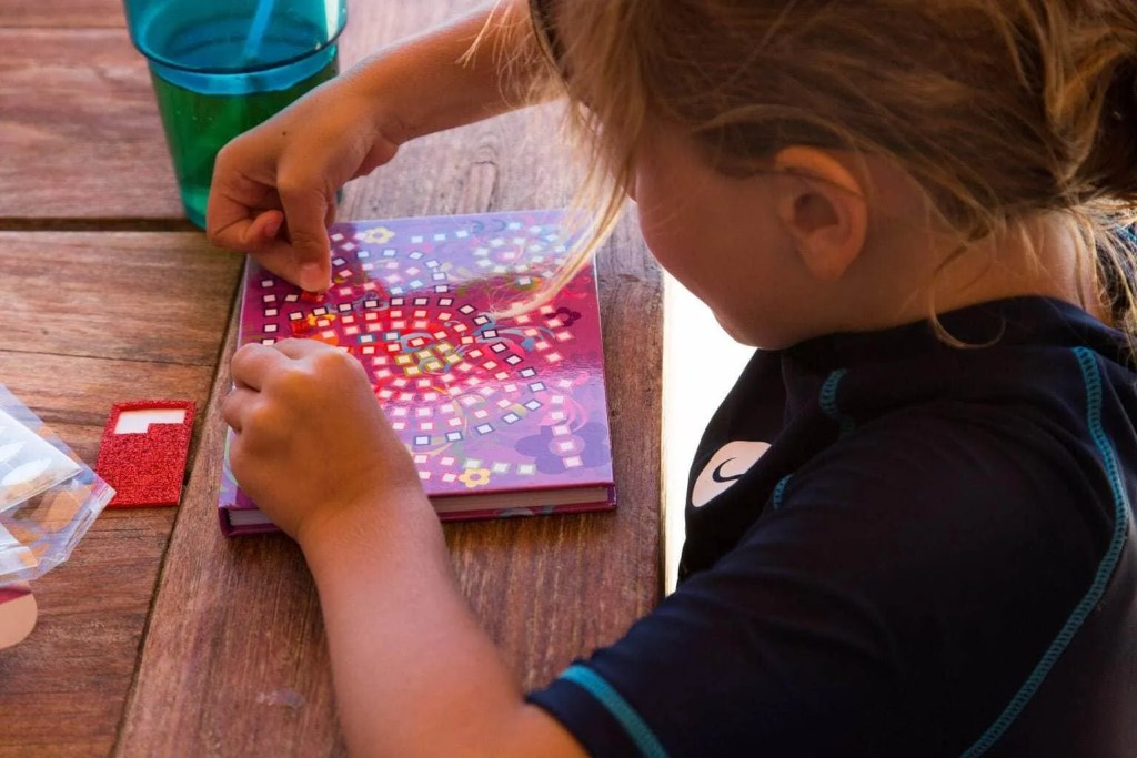 Child playing with Craft Time Mosaics, a great travel tip for families