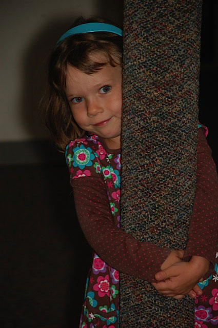 Young Girl Hugging Post