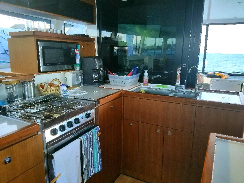 A kitchen with a stove a sink and a window Description generated with very high confidence