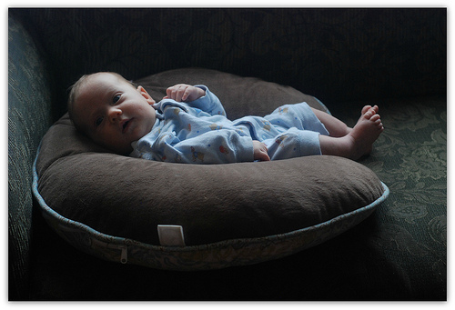 Baby in Boppy: A Study in Sweetness with Muted Shades of Brown & Green