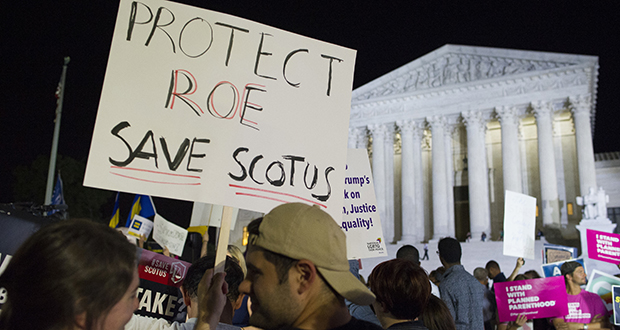 Demonstrators holds signs July 9 as they gather in front of the Supreme Court in Washington after President Donald Trump announced Judge Brett Kavanaugh as his Supreme Court nominee.  (AP file photo)