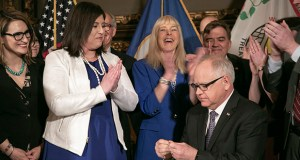 Jenny Teeson, wearing pearls at left, applauds after Gov. Tim Walz signed into law a bill, which Teeson championed, that does away with the marital rape exception. Standing between Teeson and the governor is Tesson's mom, Terri Teeson. (File photo: Kevin Featherly)