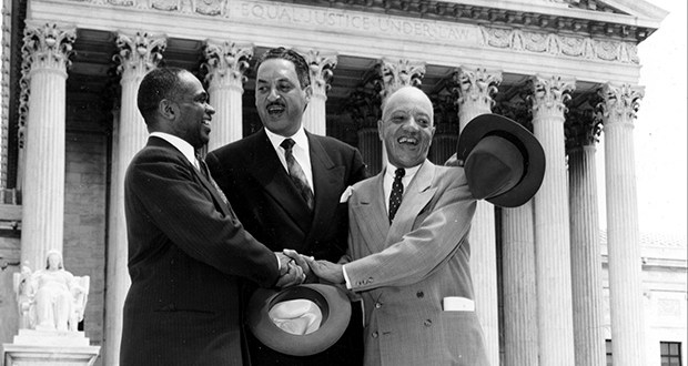 """Thurgood Marshall, center, joins hands with George E.C. Hayes, left, and James M. Nabrit outside the U.S. Supreme Court in Washington on May 17, 1954. The three lawyers successfully argued for the abolition of the """"separate but equal"""" doctrine in public education. Twenty years later, Justice Marshall wrote a strong dissent in Milliken v. Bradley, which recognized """"de facto"""" segregation — segregation that occurs as a result of circumstances, not law. (AP file photo)"""