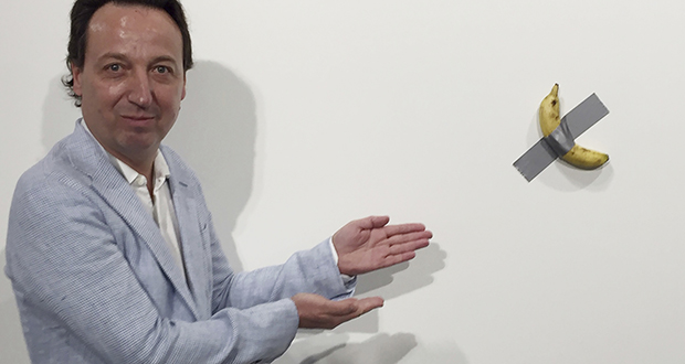"""Gallery owner Emmanuel Perrotin poses Dec. 4 next to Italian artist Maurizio Cattlelan's """"Comedian"""" at the Art Basel exhibition in Miami Beach, Florida. The work sold for $120,000. (AP file photo)"""