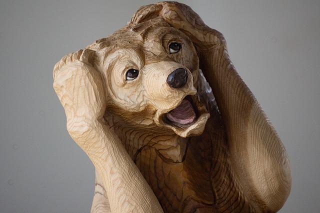 頭を抱える木彫りの熊