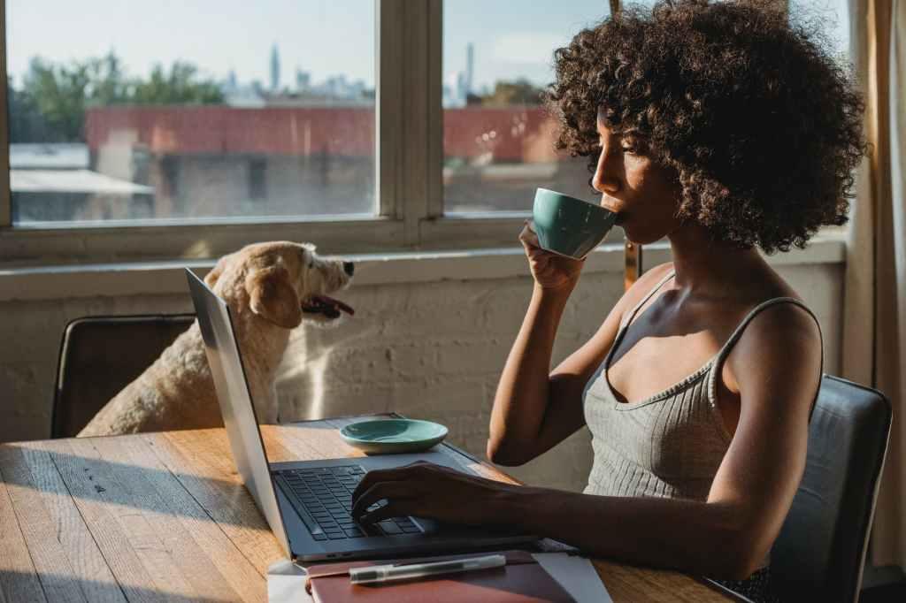 black female freelancer using laptop and drinking coffee near dog
