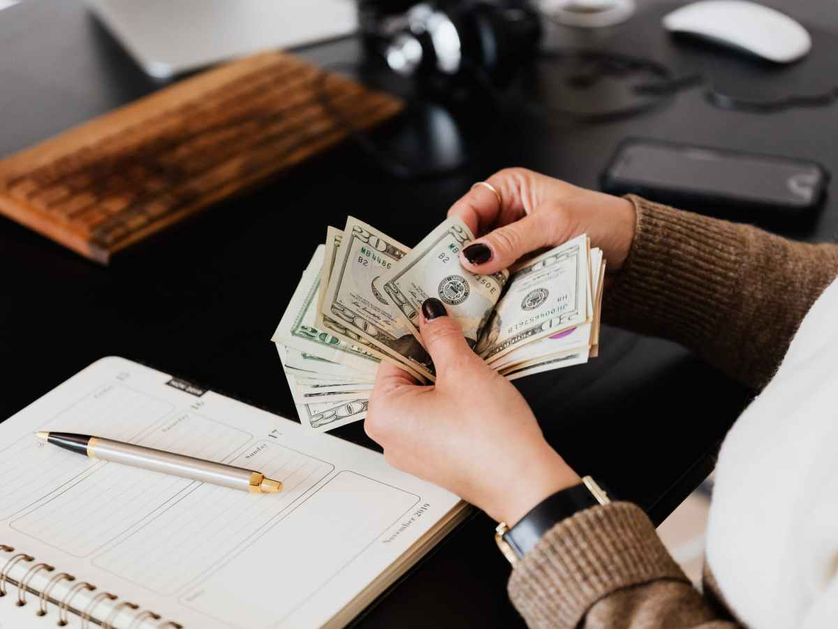 crop woman counting money at modern office table