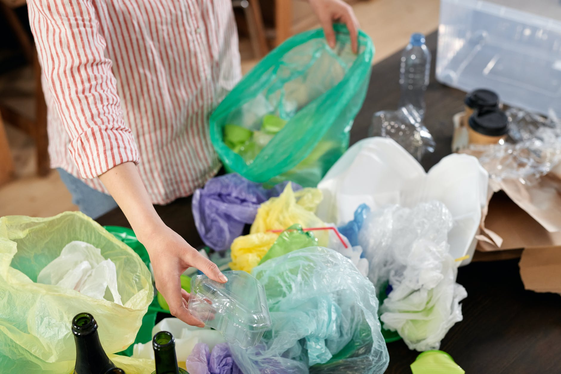 person holding green plastic bag
