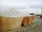 Längs med strandkanten står tält uppställda och skyddar från vinden, som under eftermiddagen kan bli lite väl kraftig.