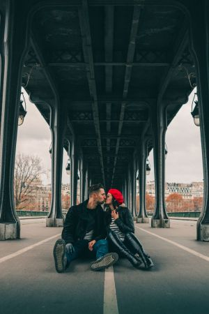 Travel Couple kissing under Pont de Bir-Hakeim in Paris