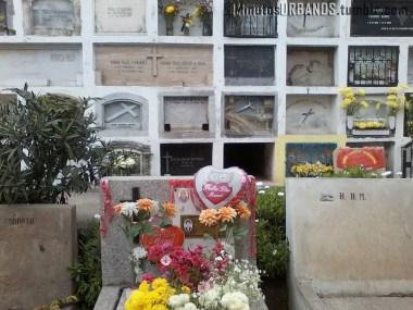 Arreglos florales y tarjetas sobre una lápida.