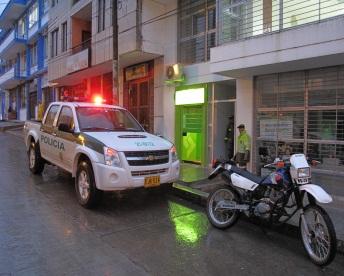 Patrulla de Policía cuidando la puerta abierta del Banco Agrario en Mocoa