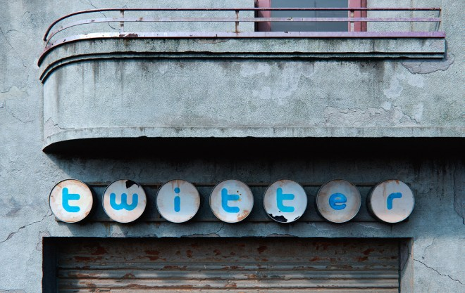 A mid-century imagining of a Twitter company sign on the side of a commercial building, but aged to the point that the sign is rusted, broken, and decaying from neglect