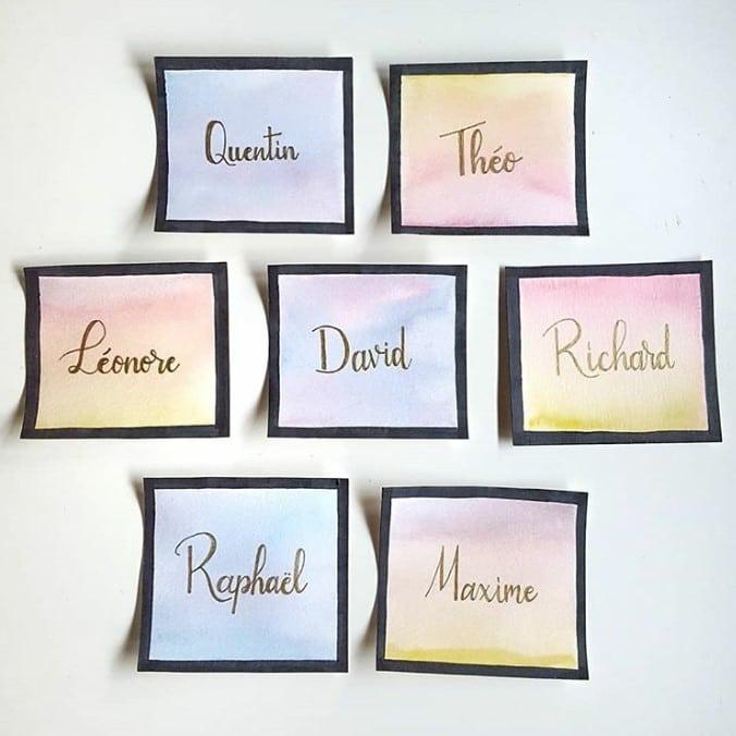 Marque-places originaux calligraphiés à l'encre métallisée sur fond d'aquarelle pour un cadeau souvenir