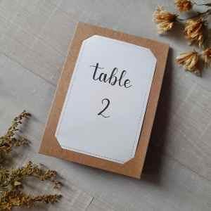 Numéro de table calligraphié pour un mariage aux tons de blanc et doré