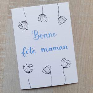"""Carte fleurie pour la fête des mères. Avec cadre fleuri de 6 coquelicots en haut en bas et un message """"Bonne fête maman"""" écrit en bleu pastel, au centre. La carte est dessinée et calligraphiée à la main."""