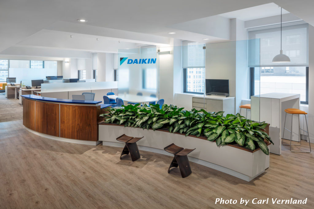 A curved reception desk, plant bed, and glass wall carry the image of airflow