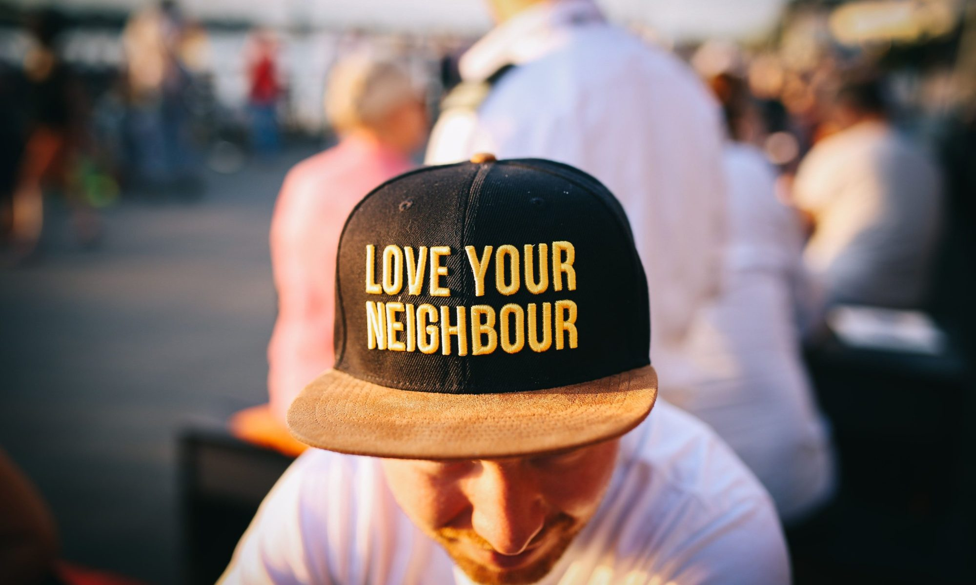 Man with cap showing Love Your Neighbour