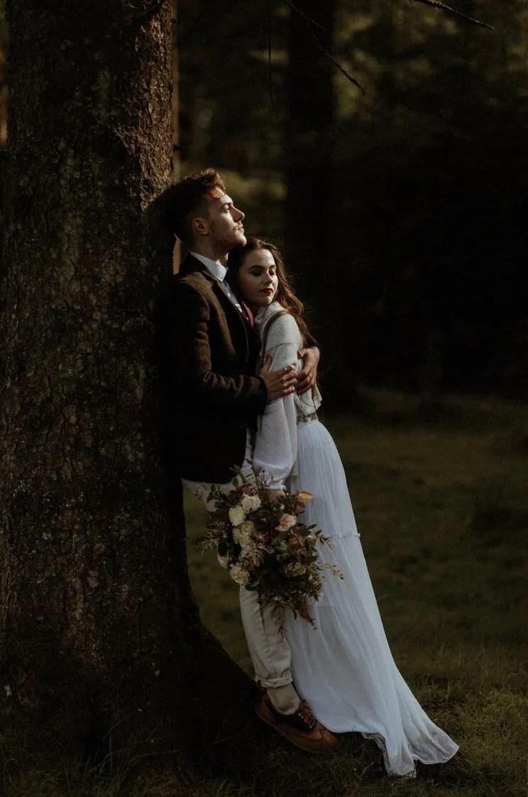 couple embracing on dartmoor with artisan wedding florist