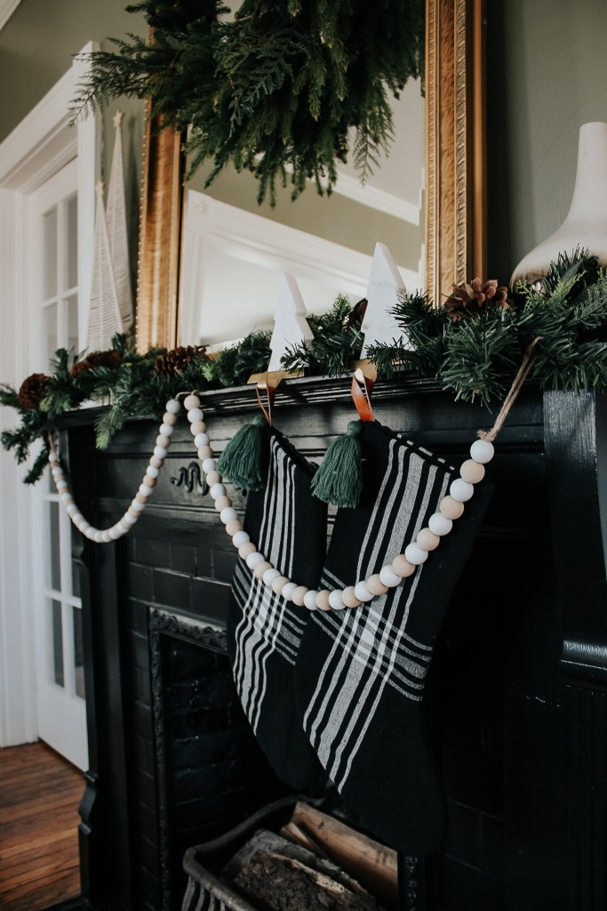 A Modern Christmas Mantle with Black stockings, greenery, garland, wood beads, macrame Christmas trees, brass and marble stocking holders, and wreath over a mirror.  Miranda Schroeder Blog ww.mirandaschroeder.com