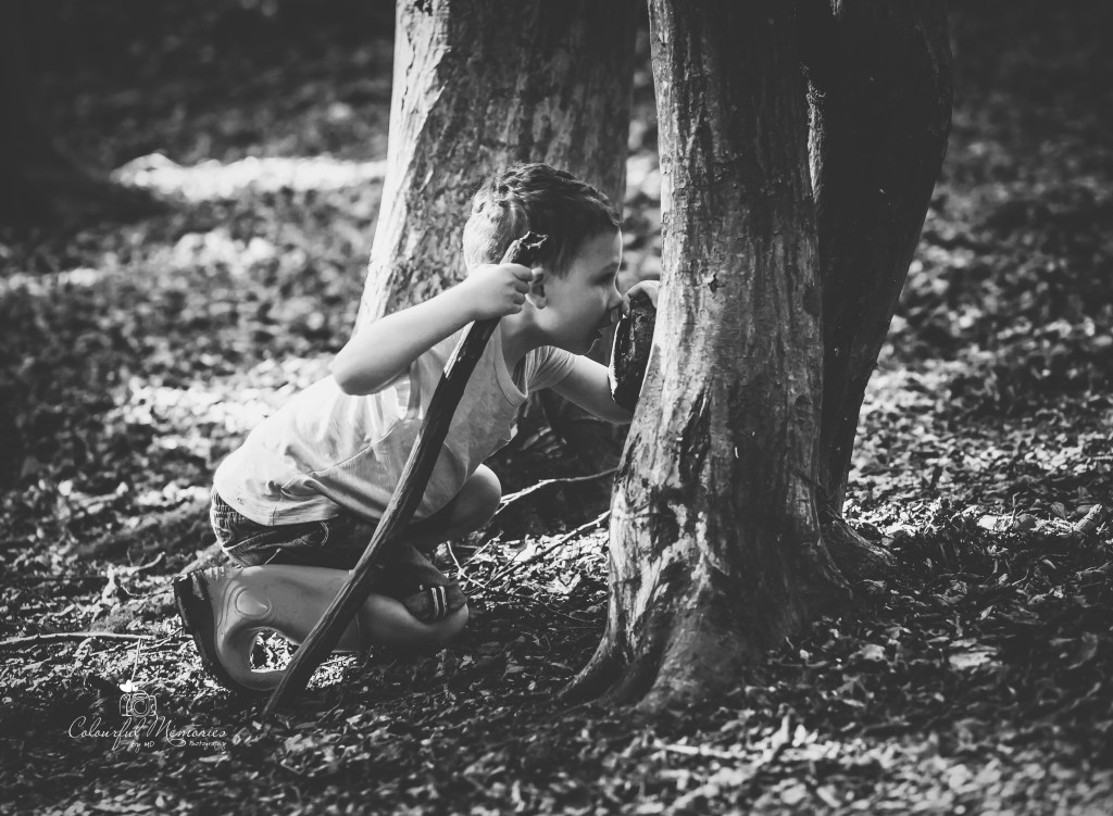 boy whispering secrets in to the tree trunk in the Hilly fields London Enfield children photographer London Family photographer