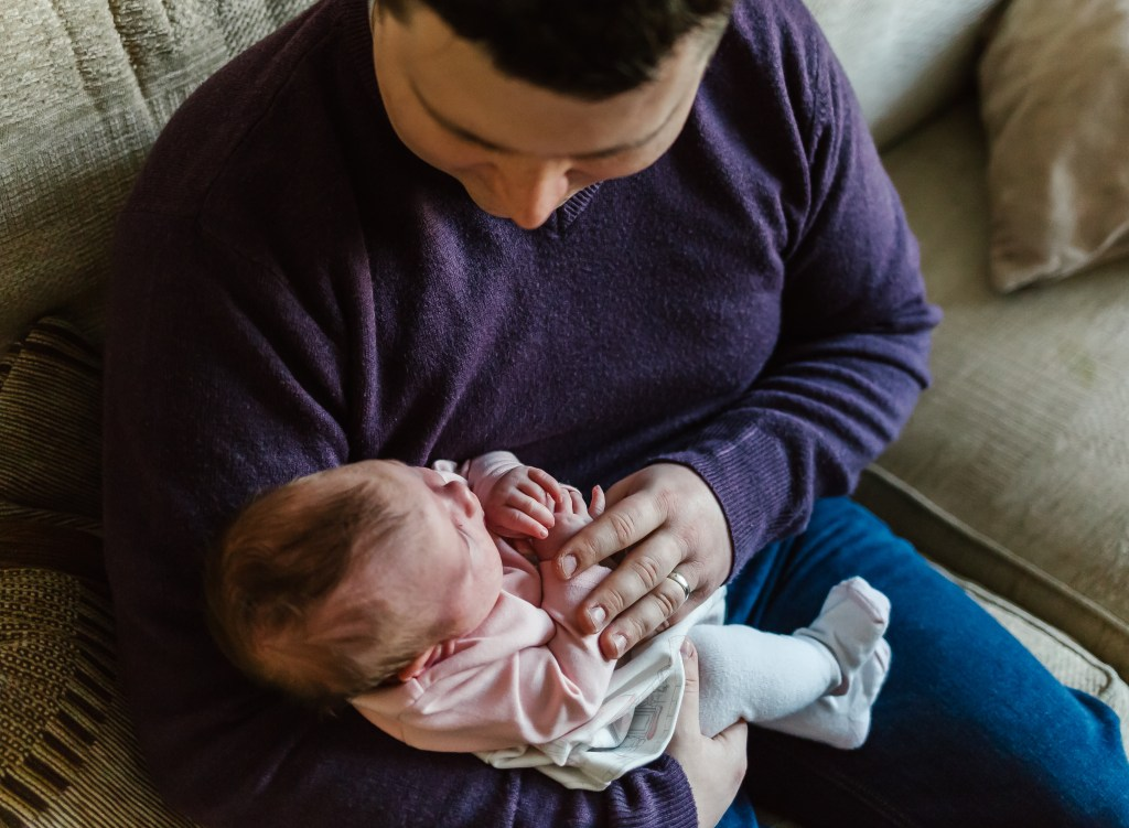 what happens at the home lifestyle photoshoot dad holding his newborn baby