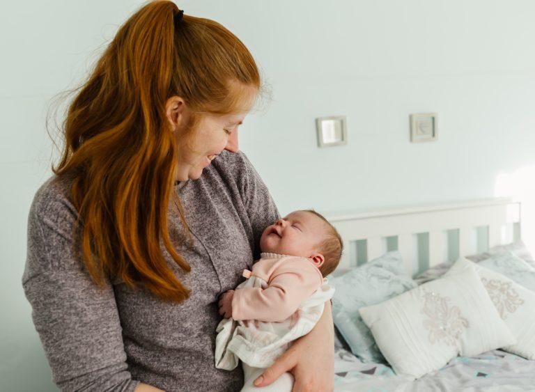 mum holding the newborn baby lovingly gazing at her newborn daughter in London South London Beckham Greenwich London photographer