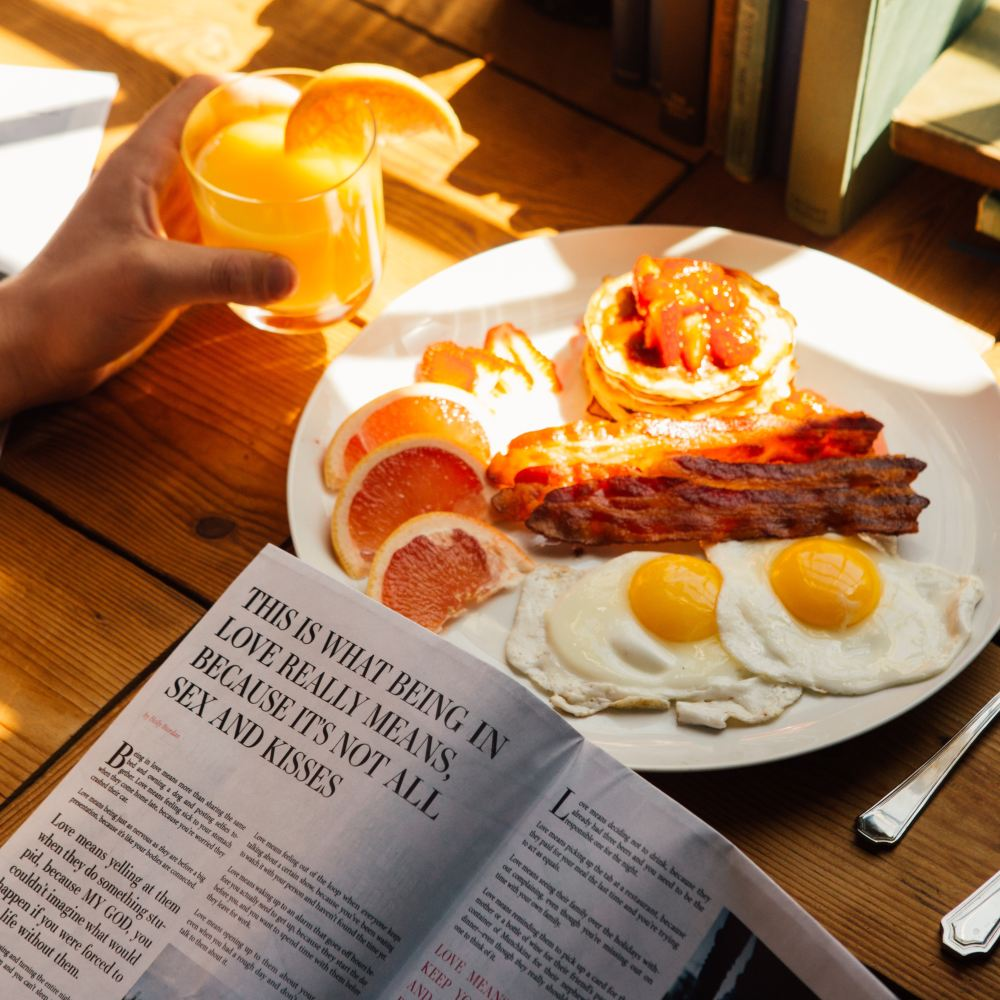 A picture of a person eating breakfast and reading a book. The breakfast includes eggs, bacon, pancakes, sliced grapefruit.