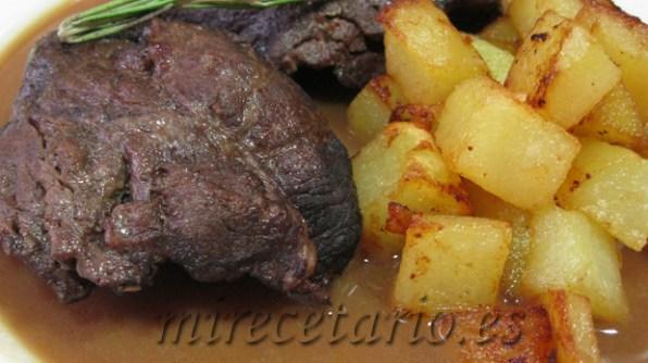 Detalle de las carrilleras y las patatas sobre la salsa