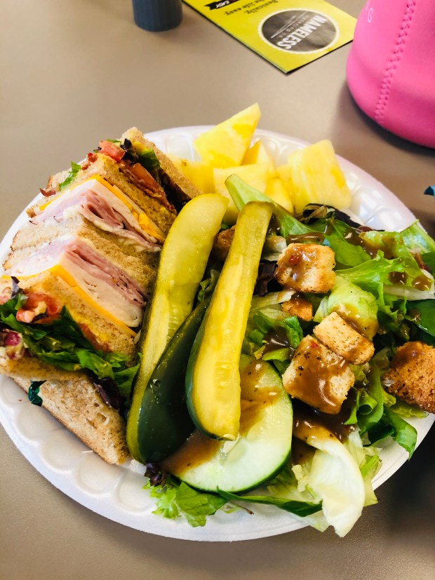 Salad, deli sandwich, pickles, and pineapple