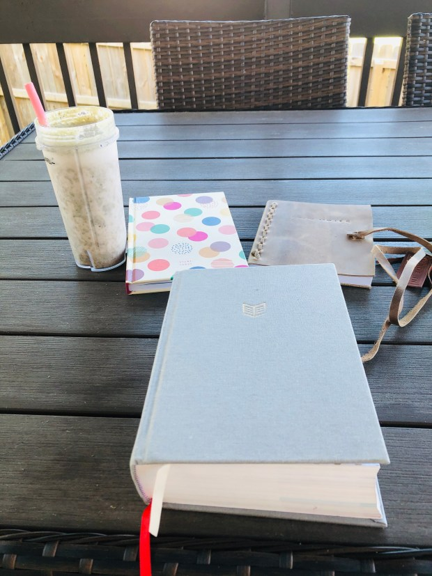 Breakfast smoothie, bible, and journal on patio