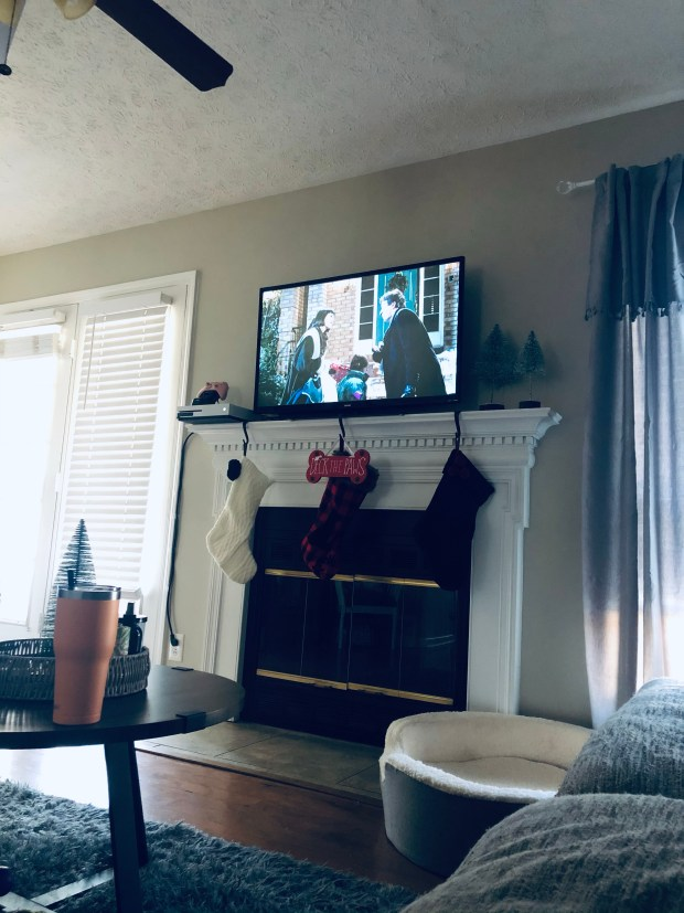Watching Christmas movie with tv on fireplace with Christmas decor