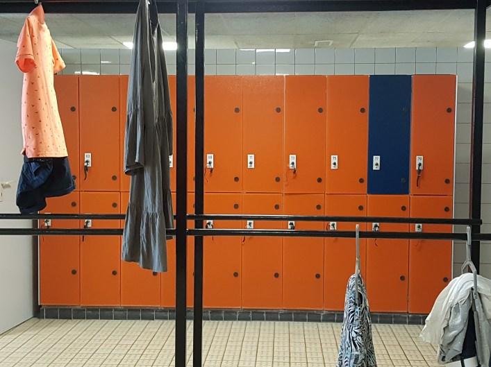 Op de achtergrond zie je 2 rijen met kluisjes, op elkaar. 10 naast elkaar, 2 boven elkaar. ze zijn allemaal oranje, op 1 na, de tweede van rechts in de bovenste rij is donkerblauw. Op de voorgrond staat een rek met kleding eraan. Aan de linkerbovenkant hangen 2 sets, aan de rechter onderkant nog 2 sets.
