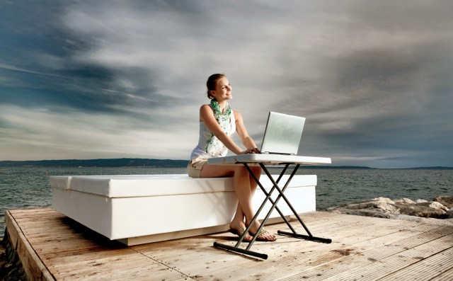Smiling woman sitting on a sofa and typing on a laptop in front of the ocean