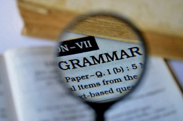 The word grammar typed in all caps and seen through a magnifying glass.
