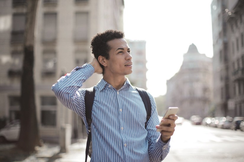 Person standing on a street holding a phone, looking confused.