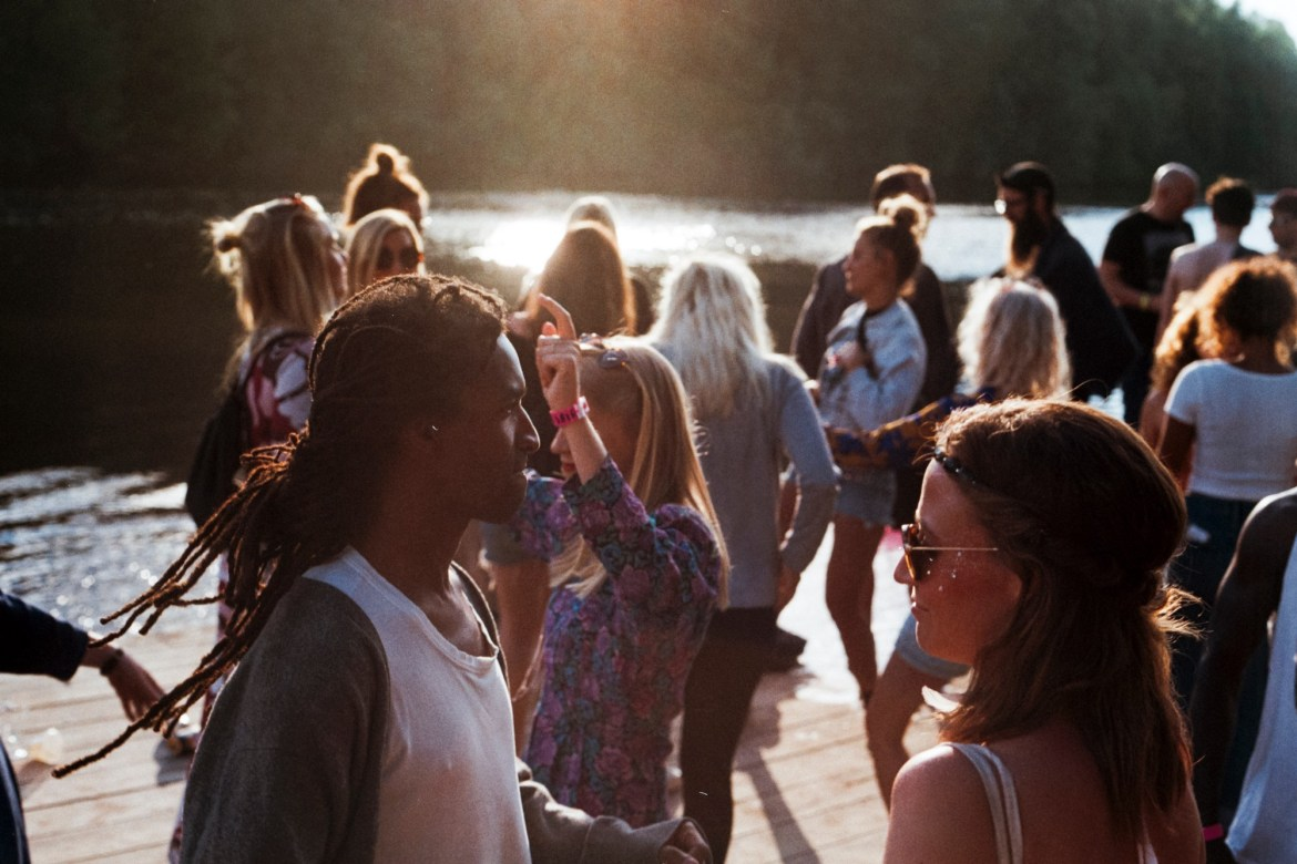 image of a large group of people by the water in the sunshine