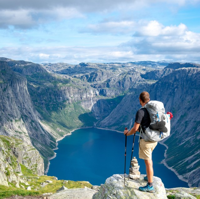 Hiker looking out over a lake and mountains.