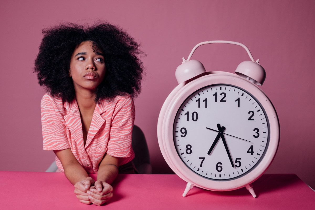 Girl looking at the clock because she's bored