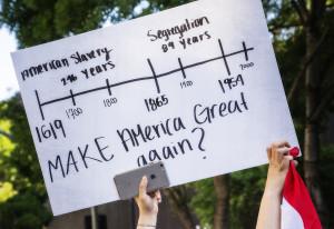 Protestors hold up a sign at a rally. Photo Credit: https://flic.kr/p/Hzb1Jq